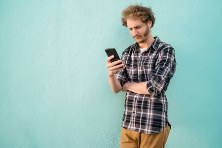 Portrait of young man using his mobile phone against blue background. Communication concept.