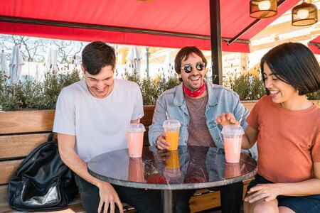 Portrait of a group of friends having fun together and enjoying good time while drinking fresh fruit juice at cafe. Lifestyle and friendship concept. Foto de archivo