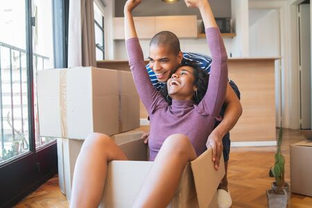 Portrait of happy latin couple having fun with cardboard boxes in new house at moving day. Real estate concept.