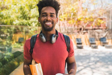 Portrait of young afro university student holding his books and looking at camera, outdoors in the campus. Education and lifestyle concept. Foto de archivo