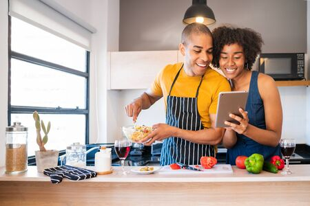 Portrait of young latin couple using a digital tablet and smiling while cooking in kitchen at home. Relationship, cook and lifestyle concept.