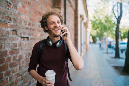 Portrait of young man talking on the phone while walking outdoors in the street. Communication and urban concept.