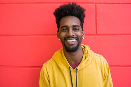 Portrait of young afro american man looking confident and posing against red wall. Foto de archivo