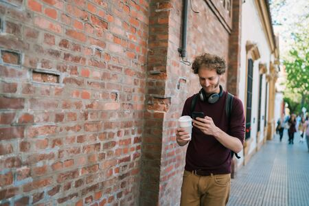 Portrait of young man using his mobile phone while walking outdoors in the street. Communication and urban concept.