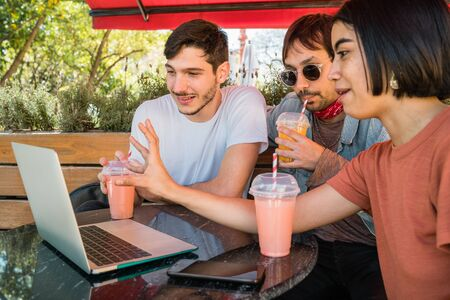 Portrait of three young friends using a laptop while sitting outdoors at coffee shop. Friendship and technology concept.