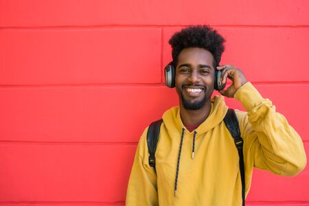 Portrait of young afro man listening to music with headphones against red background. Technology concept.