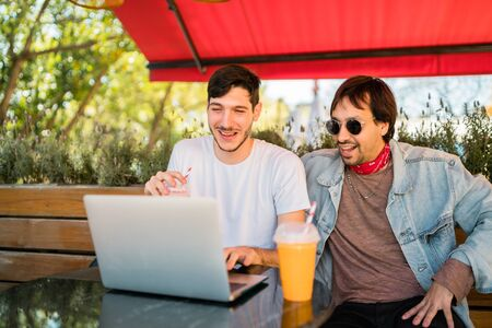 Portrait of two young friends using a laptop while sitting outdoors at coffee shop. Friendship and technology concept.