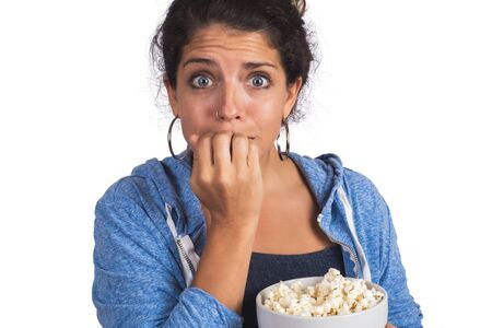 Portrait of young woman looking scared while watching a movie and eating popcorn on studio. Isolated white background.