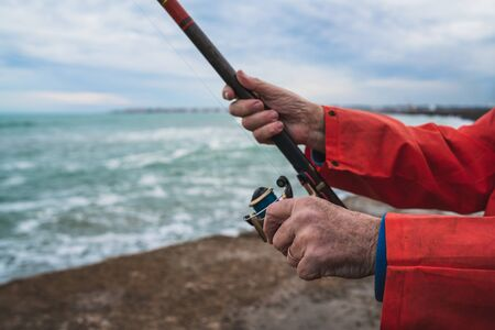 Close-up of a fisherman holding a fishing pole. Fishing and sport concept. 免版税图像