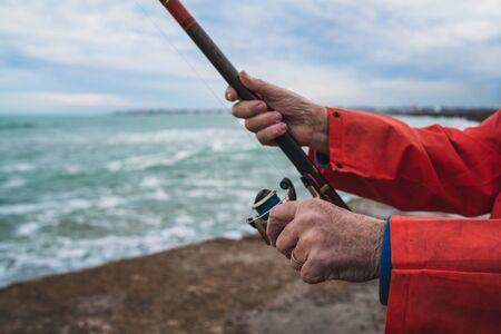 Close-up of a fisherman holding a fishing pole. Fishing and sport concept. Фото со стока