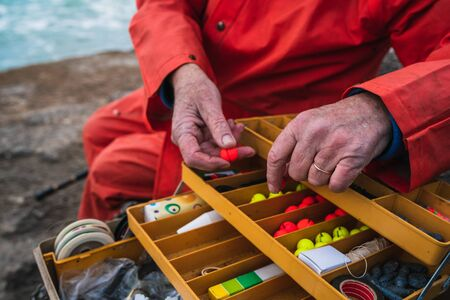 Close-up of a fisherman putting on bait with fishing equipment box. Fishing and sport concept. 版權商用圖片