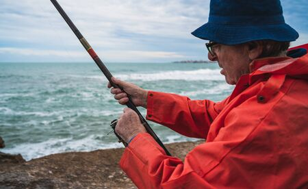Portrait of an senior man fishing in the sea, enjoying life.  Fishing and sport concept.