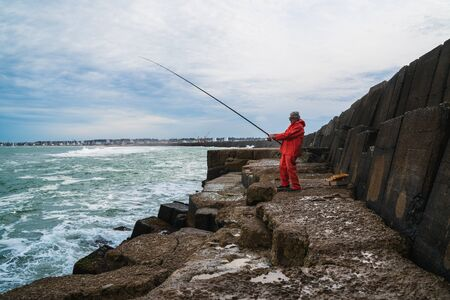 Portrait of an old man enjoying free time and fishing on the rocks at the sea. Fishing concept. Фото со стока