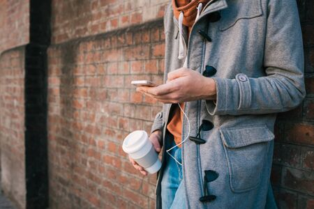 Portrait of young man with headphones and using mobile phone against brick wall. Outdoors. Urban concept.