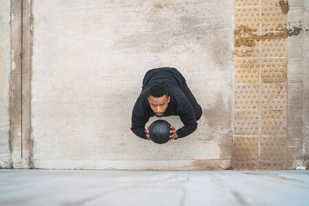 Portrait of an athletic man doing wall ball exercise outdoors. Sport and healthy concept.