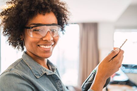Portrait of young afro woman drilling wall with an electric drill at home. Home improvement concept.