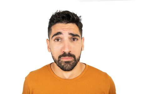 Portrait of young man feeling clueless and confused, having no idea. Isolated white background.