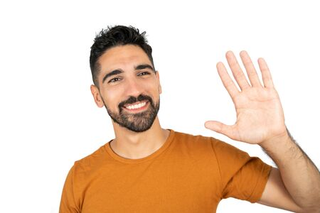 Portrait of young happy man waives hand in hello gesture while smiling against white background in studio. Banco de Imagens - 150082896