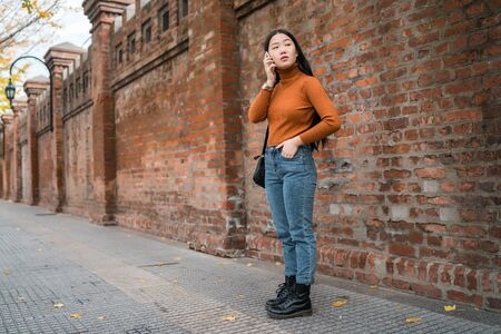 Portrait of young Asian woman talking on the phone outdoors in the street. Urban and communication concept. Фото со стока