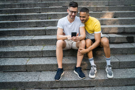 Portrait of happy gay couple spending time together while using their mobile phone. Lgbt and love concept. Stock Photo