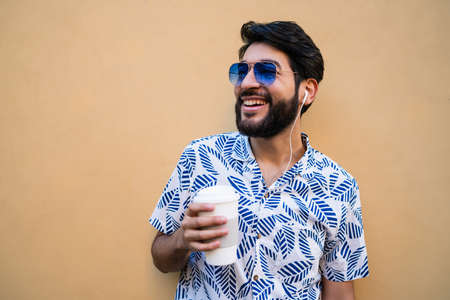 Portrait of young latin man wearing summer clothes, holding a cup of coffee and listening to music with earphones against yellow background. Stock Photo
