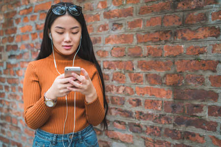 Portrait of young Asian woman using her mobile phone with earphones outdoors in the street. Urban and communication concept.