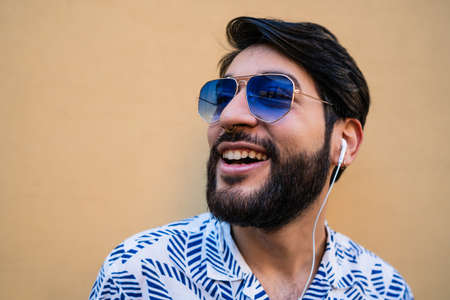 Portrait of young latin man wearing summer clothes and listening to music with earphones against yellow background.