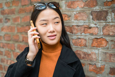 Portrait of young Asian woman talking on the phone outdoors in the street. Urban and communication concept. Stock Photo