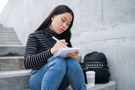 Portrait of young asian woman, writing on notebook while sitting outdoors on concrete stairs.
