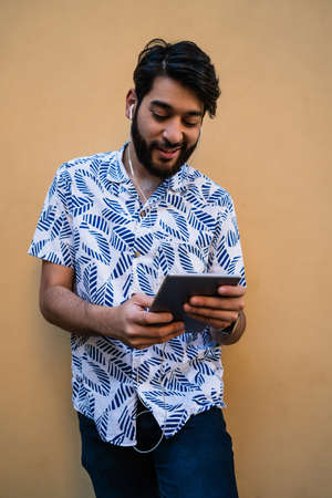 Portrait of young latin man using his digital tablet with earphones against yellow wall. Technology and urban concept. Stock Photo