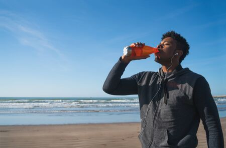 Portrait of an athletic man drinking something after training at the beach. Sport and health lifestyle.