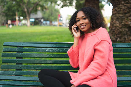 Portrait of young beautiful afro american woman talking on the phone and sitting on a bench in a park. Outdoors. 免版税图像 - 151124744