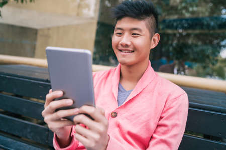Portrait of young Asian man using his digital tablet while sitting in a bench outdoors. Technology concept.