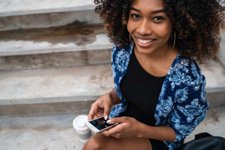 Portrait of young beautiful afro american woman using her mobile phone while sitting on concrete steps outdoors. 免版税图像 - 151124829