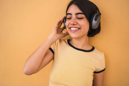 Portrait of young latin woman listening to music with headphones against yellow background. Urban concept.
