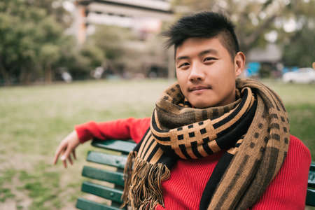 Portrait of young Asian man wearing winter clothes and relaxed sitting on a bench in a park.