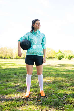 Portrait of young female soccer player standing on field and holding football ball. Sports concept.