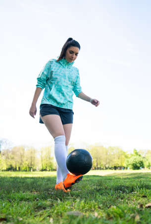 Portrait of young woman practicing soccer skills and doing tricks with the football ball. Soccer player juggling the ball. Sports concept. Foto de archivo