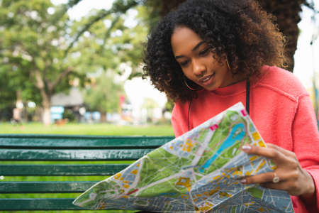Portrait of young beautiful afro american woman sitting on bench in the park and looking at a map. Travel concept. Outdoors.