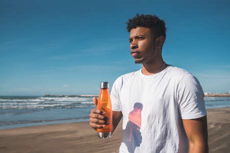 Portrait of a sport man holding a bottle of water at the beach. Sport and health lifestyle.