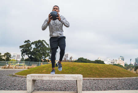 Portrait of an athletic man training with medicine ball at the park outdoors. Sport and healthy concept.