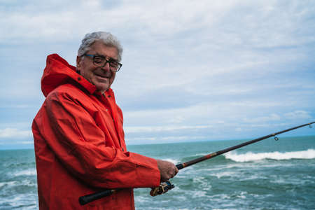 Portrait of an senior man fishing in the sea, enjoying life. Fishing and sport concept. Stock Photo