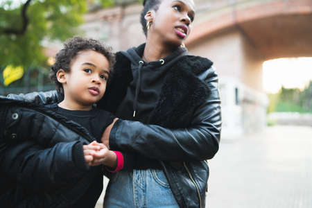 Portrait of an African american mother with his son standing outdoors in the park, having fun. Single parent family. 版權商用圖片