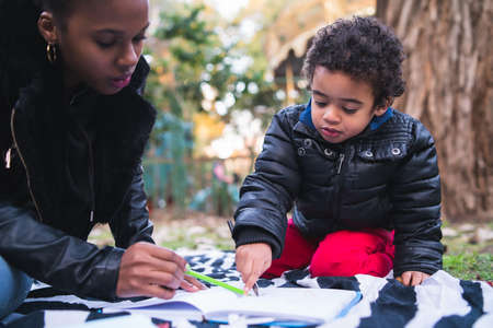 Portrait of an African american mother with his son playing and having fun together outdoors in the park. Single parent family. 版權商用圖片