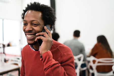 Afro businessman talking on the phone and working at his workplace. Business concept.