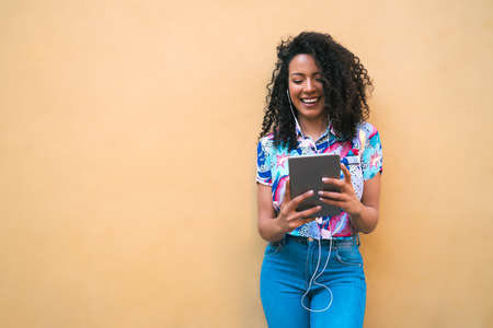 Portrait of young happy afro american latin woman listening music on her digital tablet. Technology concept.