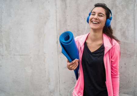 Portrait of an athletic woman holding a training mat while listening to music. Sport and lifestyle concept.