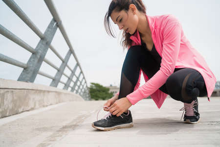 Portrait of an athletic woman tying her shoelaces and getting ready for jogging outdoors. Sport and healthy lifestyle concept.