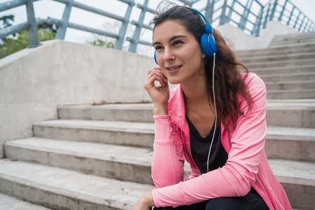 Portrait of an athletic woman listening to music on a break from training while sitting on stairs. Sport and health lifestyle concept.
