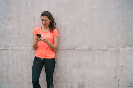 Portrait of an athletic woman using her mobile phone on a break from training. Sport and health lifestyle. 免版税图像